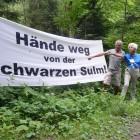 Freda Meissner-Blau und Ulrich Eichelmann vor Transparent im Lager